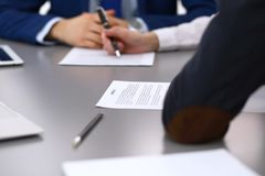 Group of business people and lawyer discussing contract papers sitting at the table, closeup. Businessman is signing. Document after agreement done Stock Photo