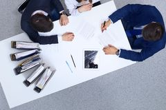 Group of business people and lawyer discussing contract papers sitting at the table, view from above. Businessman is. Signing document after agreement done royalty free stock photo