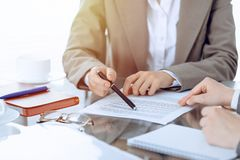 Group of business people or lawyers discussing contract papers sitting at the table, close-up. Group of business people and lawyers discussing contract papers stock photography