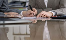 Group of business people and lawyers discussing contract while sitting at the table. Woman chief is taking pen for. Signing papers. Close-up of human hands at Stock Photography