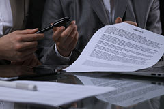 Group of business people and lawyers discussing contract sitting at the table. Woman chief is taking pen for signing Royalty Free Stock Photos