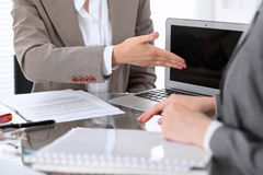 Group of business people or lawyers at meeting  discussing contract papers. Woman pointing into laptop computer monitor Stock Photos