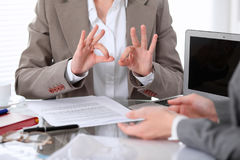 Group of business people or lawyers at meeting  discussing contract papers. Woman showing ok sign Stock Image