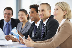 Group Of Business People Listening To Colleague Addressing Office Meeting Stock Photos