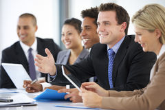 Group Of Business People Listening To Colleague Addressing Office Meeting Stock Images