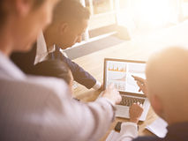 Group of business people looking at graphs on a laptop Royalty Free Stock Image