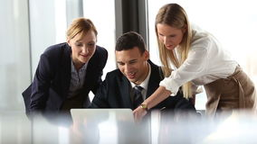 Group of business people looking at laptop and discussing