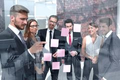 Group of business people looking at notes on glass royalty free stock photography