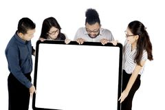 Business people holding whiteboard on studio. Group of business people looks amazed while holding a blank whiteboard, isolated on white background Royalty Free Stock Photography