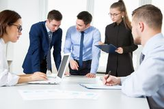 Business people working in an office. Group of business people at a meeting around a table in a modern office Royalty Free Stock Photo