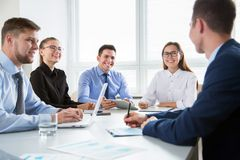 Group of business people. At a meeting around a table in a modern office Royalty Free Stock Photos