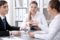 Group of business people at meeting on the background of office. Focus at a beautiful brunette woman stock image