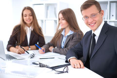 A group of business people at a meeting on the background of office. Focus on a businessman Royalty Free Stock Images