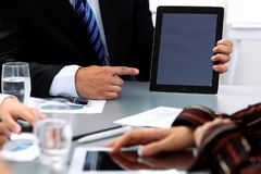 Group of business people at meeting, close up. Boss pointing into tablet computer monitor Royalty Free Stock Photos