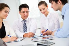 Group of business people at a meeting. Around a table in a modern office Stock Photos