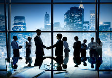 Group of business people and men shaking hands. Reflected onto table with documents Stock Images