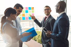 Group of business people with notes on window Stock Image