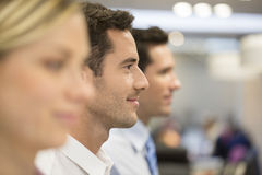 Group of business people at the office lined up, focus on man Stock Photography