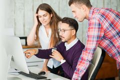 Group of business people in office near computer monitor. Discuss smile point at something. Business concept Stock Photography