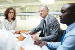 Briefing of financiers. Group of business people with papers discussing financial questions at briefing Stock Photos