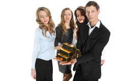 Group of business people and the pyramid of gold bars. Team of young businessmen in suits official shows a pyramid of gold bars Royalty Free Stock Photo