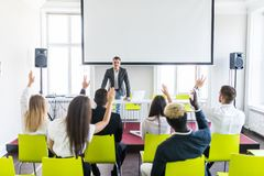 Group of business people raise hands up to agree with speaker in the meeting room seminar. Ask presenter. Group of business people raise hands up to agree with royalty free stock images