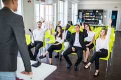 Group of business people raise hands up to agree with speaker in the meeting room seminar. Ask presenter. Group of business people raise hands up to agree with royalty free stock photography