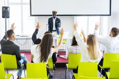 Group of business people raise hands up to agree with speaker in the meeting room seminar. Business meeting. Group of business people raise hands up to agree stock photos