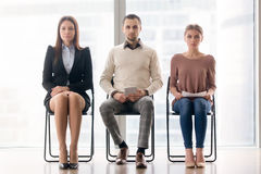 Group of business people sitting on chairs looking at camera Stock Photos