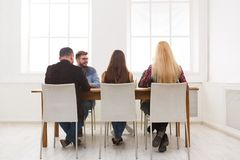 Group of business people sitting in office. Group of business people sitting at conference table at office, back view. Successful team having conversation stock image