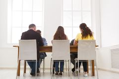 Group of business people sitting in office. Group of business people sitting at conference table at office, back view. Successful team having conversation royalty free stock photo