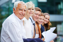 Group of business people sitting outdoors Stock Image