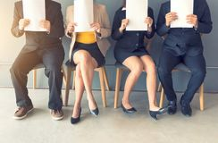 Group of business people is sitting in a row in an office lobby stock photography