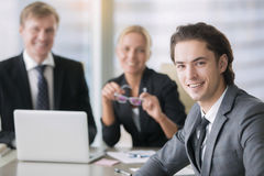 Group of business people and a smiling young man. Group of business people, partners together to establish and grow a business, portrait of young men with royalty free stock photography