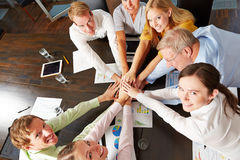 Group of business people stacking hands. Group of happy business people stacking hands on a desk from above Royalty Free Stock Photo