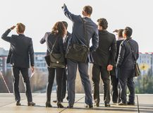 A group of business people stand on a platform while one points into the distance Stock Photography