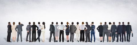 Group of business people standing in front of blank grey background Stock Images