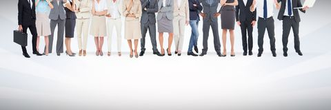 Group of business people standing in front of blank grey background. Digital composite of Group of business people standing in front of blank grey background Royalty Free Stock Photography