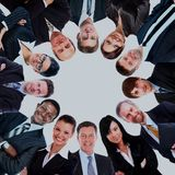 Group of business people standing in huddle, smiling, low angle view. Stock Photo