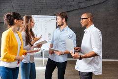 Group of business people standing and talking in conference room. Multiethnic group of smiling young business people standing and talking in conference room Royalty Free Stock Images
