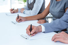 Group of business people taking notes Stock Image