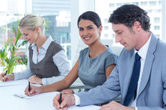 Group of business people taking notes Royalty Free Stock Image
