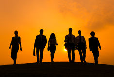 Group  of Business People Walking in Back Lit Stock Photography