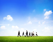 Group Of Business People Walking Through The Field In Daylight.  Stock Photo