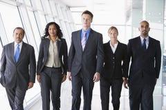 Group of business people walking towards camera. Group of business people walking through office towards camera Stock Image