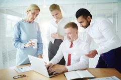 Online conference. Group of business people watching teleconference in front of laptop in office Royalty Free Stock Photo