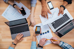 Group of business people working for a financial report. Top view of group of business people using cell phones and laptops and working for a financial report stock photography
