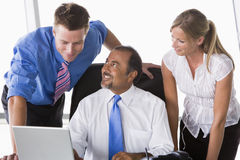 Group of business people working in office. Looking at laptop Stock Image