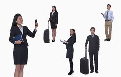 Group of business people working, taking photos, texting, studio shot, full length Royalty Free Stock Photos