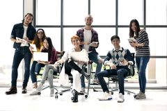 Group of business persons. Each holding an electronic device or gadget looking happy and joyful in a casual office Royalty Free Stock Images